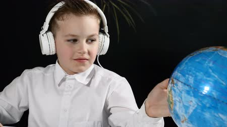 scholar : School concept. Cute boy sits at a desk with globe on it and a blackboard behind him. boring schoolboy turns globe round and points at a random place Stock Footage