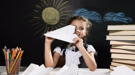 scholar : School concept. Attractive girl sit with paper plane in hand. Desk and blackboard behind them. Schoolgirl throw planes and smiles.