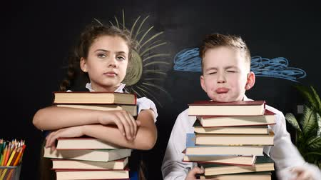 scholar : School concept. Cute boy and attractive girl sit with heaps of books. Schoolkids sit by desk. blackboard behind them. Schoolchildren hug books being upset a little Stock Footage