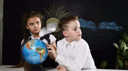 de volta : School concept. Schoolkids sit at a desk playing with a globe on it. Children choose a place to travel on vacation