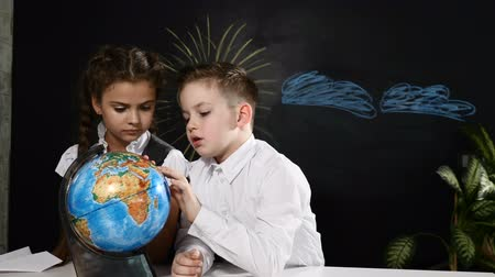scholar : School concept. Schoolkids sit at a desk playing with a globe on it. Children have fun pointing at random places