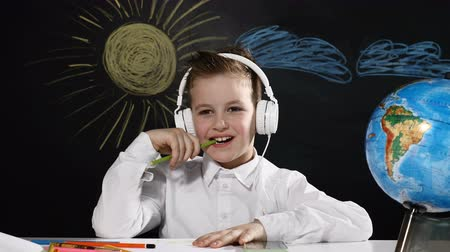 scholar : School concept. Cute boy sits at a desk with globe on it and a blackboard behind him. smiling schoolboy with headphones on head puts pencil into mouth Stock Footage
