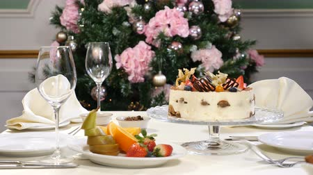toalha de mesa : Restaurant concept. New Year and Merry Christmas feast table. Waiter in gloves opens and then closes glass dish with a fruit cake