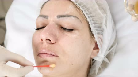 cotton swab : Beauty concept. Young female client gets beauty facial procedure. face renovation. Beautician uses cotton bud to cover face skin with beauty mask