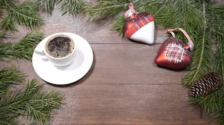 kužel : New Year and Christmas postcard art. Fir tree, a cup of fresh-brewed coffee and Christmas-tree decoration placed on wooden background. Top view.a space for a note in the middle
