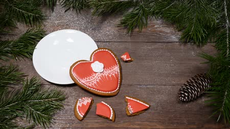латте : Food art. Broken heart. Fir tree, a cup of fresh-brewed coffee and heart-shaped gingersnaps placed on wooden background.one cookie is broken into pieces Top view. Female hands takes out a cup Стоковые видеозаписи