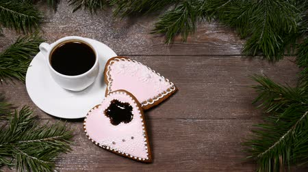 латте : Food art. Good morning concept. Fir tree as a frame, cup of coffee and 2 heart-shaped gingersnaps are on wooden background.
