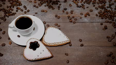 bekap : Food art. Good morning concept. cup of coffee and 2 heart-shaped gingersnaps are on wooden background. Coffee beans fall down in slow motion