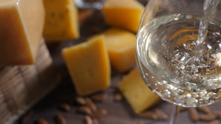 cheese piece : Food art. Different sorts of cheese beautifully arranged on wooden background. Top view. White wine is being poured into glass. Extra slow motion. Stock Footage