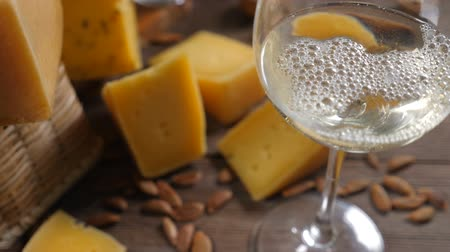 pieces of cheese : Food art. Different sorts of cheese beautifully arranged on wooden background. Top view. White wine is being poured into glass. Extra slow motion. Stock Footage
