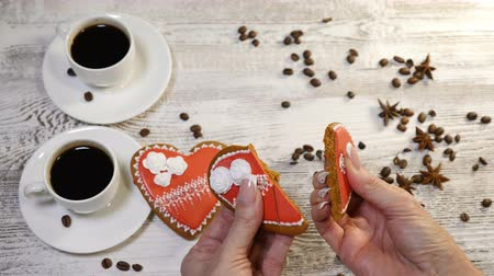 szív alakú : Food art. Broken heart concept. 2 cups of freshbrewed coffee and 2 heartshaped Gingerbread Cookies placed on wooden background with coffee beans around. Female hands take a cookie and break it Stock mozgókép