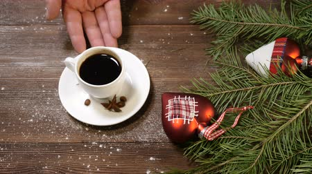 pontilhado : New Year and Merry Christmas. christmas tree with decorations on wooden background. Female hand puts a cup of freshbrewed coffee. Stock Footage