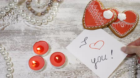 szív alakú : Love relations. Saiint valentine day. Two heartshaped ginger cookies and burning candles on wooden background. Female hand puts a I love you note