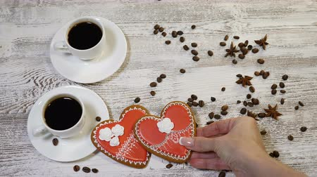 szív alakú : Food art. Love and Saint valentines concept. 2 cups of freshbrewed coffee and a heartshaped Gingerbread Cookie placed on wooden background with coffee beans around. Female hands puts another cookie Stock mozgókép