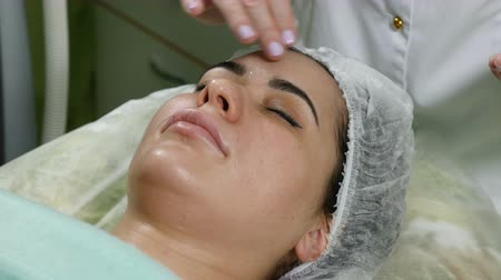 kraliçe : Beauty clinic concept. Close-up of beautician spreading cream before facial procedure. Young woman . Facial rejuvenation. 4k