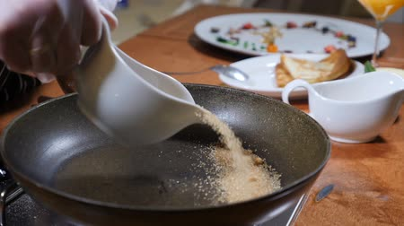 cukros : Food preparation. Chef pours cane sugar on pan to prepare caramel sauce. Slow motion