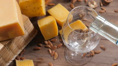 bílé víno : Wine and cheese. Food art. Different sorts of hard cheese beautifully surved on a wooden background. White wine is being poured into wine glass.