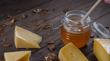 twaróg : Cheese and honey. Variety of hard cheese is on wooden background. Honey on honey stick. Slow motion