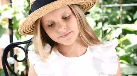 hair growth : Portrait of blond girl in a white dress and straw hat, enjoying sunny day in open terrace of restaurant. Young female kid holds homemade pastry