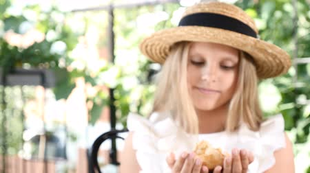 vdolky : At first out of focus zoom in focus. Portrait of cute little girl holding Freshly baked coffee caked covered with nuts. Girl showing hands with cake to camera. 4k