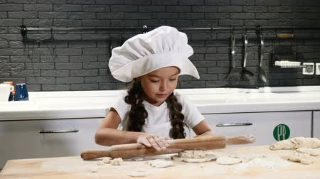 cooking pots : Kid chef concept. Little pretty girl in chef hat and chef apron cooking with dough. Young cooker holds Rolling pin. 4k