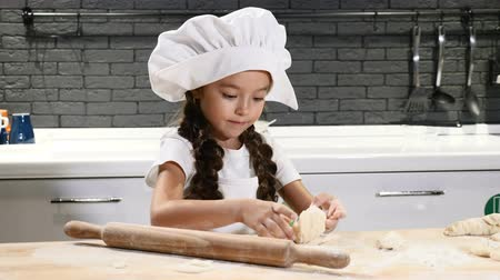 kepçeli : Children cooking. Little girl in chef hat playing with dough and rolling pin. Laughing having fun in kitchen. 4k Stok Video