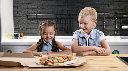calabresa : Kids eating. Two pretty kids opening pizzabox and watching pizza in delight. Favourite food for children. 4k