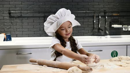 слойка : Little pretty girl in chef hat and apron. Kid chef concept. Adorable girl playing with dough. 4k Стоковые видеозаписи