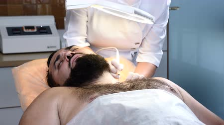 melanoma : Brutal darkhaired man in healthcare clinic. Dermatologist makes electrocoagulation. 4k Stock Footage