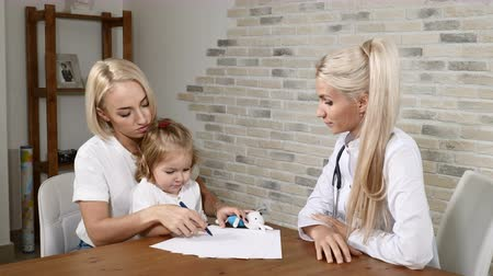 pediatria : Family clinic. Pretty mother and her female kid in doctors office.Child drawing while mother and doctor talking. General practicioner working. 4k