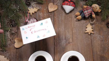 przyszłość : Merry Christmas and happy new year concept. Cups of coffee placed on wooden background together with fir tree branches and heartshaped toys. White note is put near cups