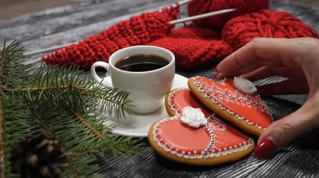 szív alakú : Cup of coffee and 2 red heartshaped ginger-snaps placed on a wooden background near fir tree branches and red yarn with knitting needle. Female hand puts one cookie on another. hd