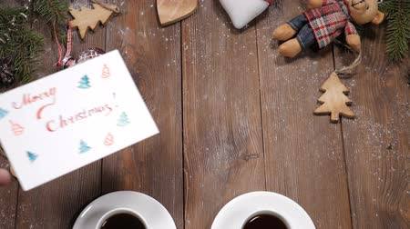 szív alakú : Merry Christmas and happy new year concept. Cups of coffee placed on wooden background together with fir tree branches and heartshaped toys. Merry christmas note is put near cups