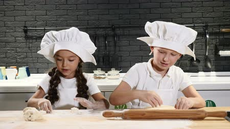 Children cooking in kitchen. Two little kids in chef hats roll dough smiling having fun. 4k