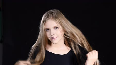 Portrait of adorable girl posing looking at camera. Smiling and touching her hair. Blond pretty teen girl with long hair on black background. 4k