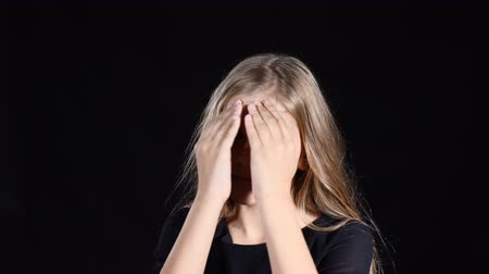 Portrait shot of blond attractive teen girl with long hair posing in front of camera. Girl closes face with hands opens showing different emotions. Angry. joy, sad.
