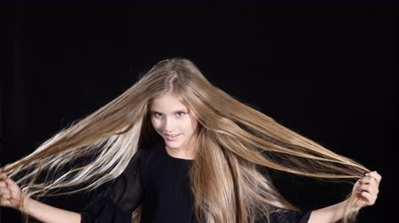 Portrait of adorable girl posing looking at camera. Smiling and touching her hair. Blond pretty teen girl with long hair on black background.