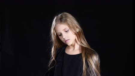 Model girl posing on black background. Blond longhaired teenager looking at camera showing face emotion. 4k
