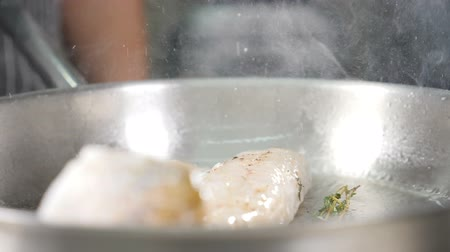 Cooking pan-fried fish fillet in steel frying pan with oil on electric stove. Splashes in slow motion. Restaurant cuisine. Close up. Shot in hd