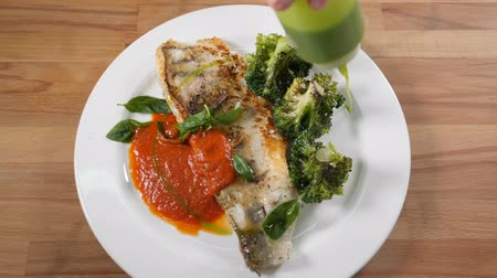 Top view on dish with fried fish fillet served with green broccoli. Male chef hand holding sauce boat. Mouthwatering sauce being poured onto dish. Slow motion. Shot in hd Filmati Stock