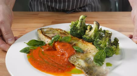 olasz konyha : Michelin-starred restaurant food concept. Male chef holding plate with fish dish served with green broccoli. cook serves ready-made dish. Slow motion. Shot in hd