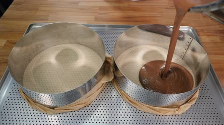 Pouring chocolate cake mixture into tins. Making Chocolate Layer Cake. Culinary concept. Slow motion. Shot in hd Wideo
