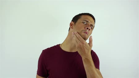 tıraş : A handsome young man touches his face and is about to shave. Stok Video
