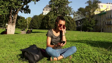 jovial : Beautiful girl sits on the grass in the park and listens to her favorite melody through the headphones in the phone, shaking her head to the beat of the music.