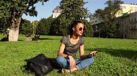 jovial : Beautiful girl sits on the grass in the park and listens to her favorite melody through the headphones in the phone, dances and shakes her head to the beat of the music.