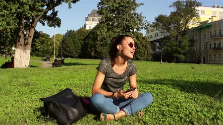 jovial : Beautiful smiling young girl sits on the grass in the park and listens to her favorite melody through the headphones in the phone, dances and shakes her head to the beat of the music.