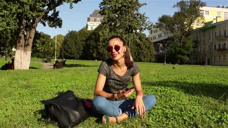 jovial : beautiful smiling young girl sitting on the grass in the park on a sunny afternoon and listening to her favorite melody in the phone, dancing and shaking her head to the beat of the music.
