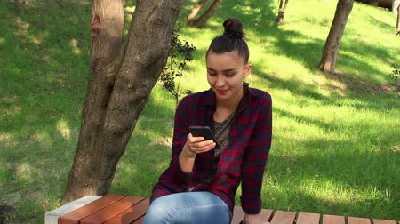 pléd : Young beautiful girl in a plaid shirt sits on a bench in the park, actively rewritten in internet chat Stock mozgókép