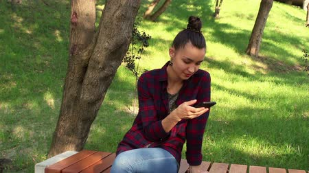 pléd : Young beautiful girl in a plaid shirt smiling and browsing the tape of social networks in her smartphone. Stock mozgókép