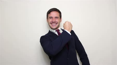 humor : Handsome young businessman actively expresses joy, makes a gesture with his hand and says yes. Stock mozgókép